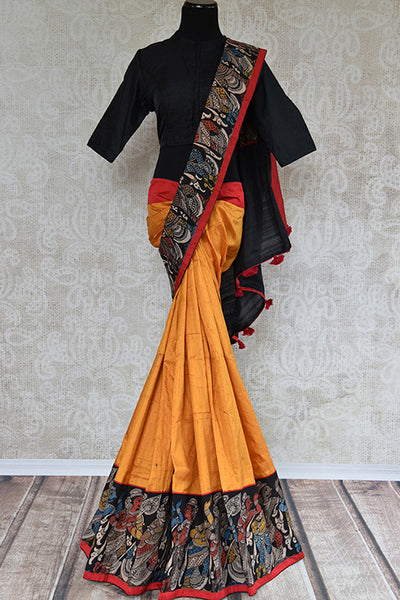 It's yellow raw silk, printed sari with black blouse and pallu. Has figure design in the border, thin red border. Blouse has yellow color in back and figure. front view