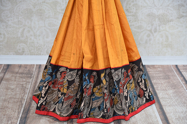 It's yellow raw silk, printed sari with black blouse and pallu. Has figure design in the border, thin red border. Blouse has yellow color in back and figure. bottom view