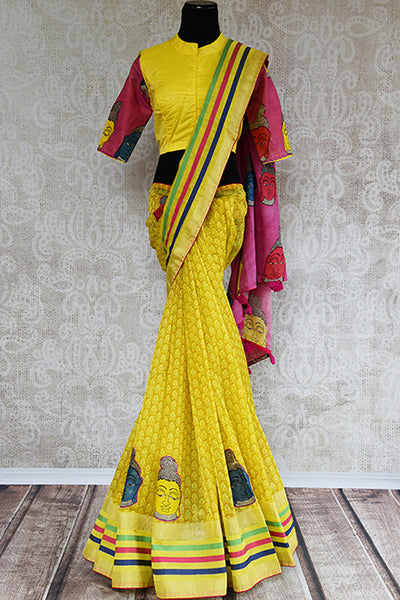 It's a yellow kalamkari printed sari with geometric pattern in the bottom. Blouse is yellow colored with pink sleeves. sari has human figure design and pink pallu - front view