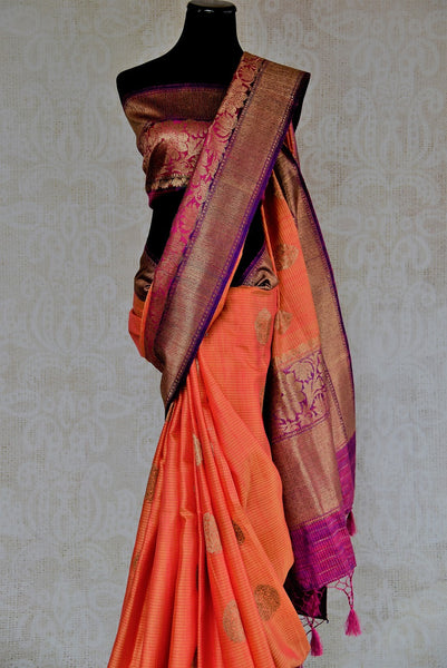 90D318 Lovely peach, pink & purple sari with pops of golden that is a perfect Indian outfit for weddings. Buy this muga tussar Banarasi traditional sari at our ethnic wear store online in USA. It's sure to keep all eyes on you wherever you go!