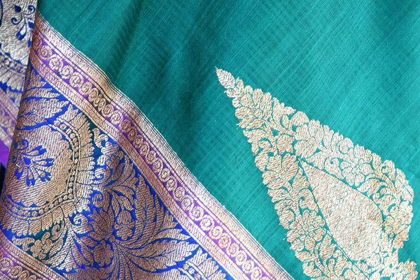 90D323 A faultless and timeless choice in traditional Indian wear, this green muga tussar Banarasi saree with a heavy border and heavy pallu is available at our ethnic wear store is perfect for Indian weddings and festive occasions.