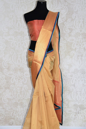 90D324 Beige maheshwari silk saree with a silk patti & a bold blue trim available online at our ethnic wear store. The simple sari is ideal for Indian weddings and pujas and can be styled in a whole lot of ways!