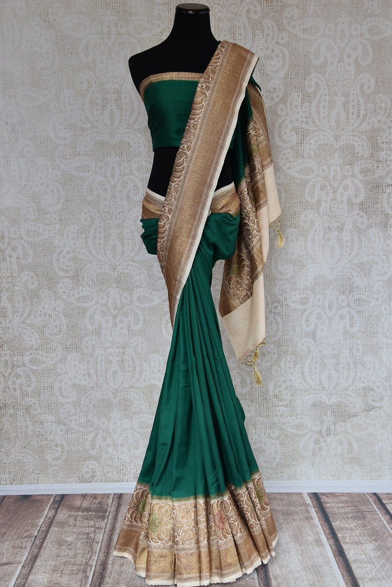 90D344 Emerald green muga banarasi saree with traditional Indian patterned beige border. Buy this Indian saree, ideal for pujas & small functions online at our ethnic clothing store - Pure Elegance and get set to wow wherever you go!