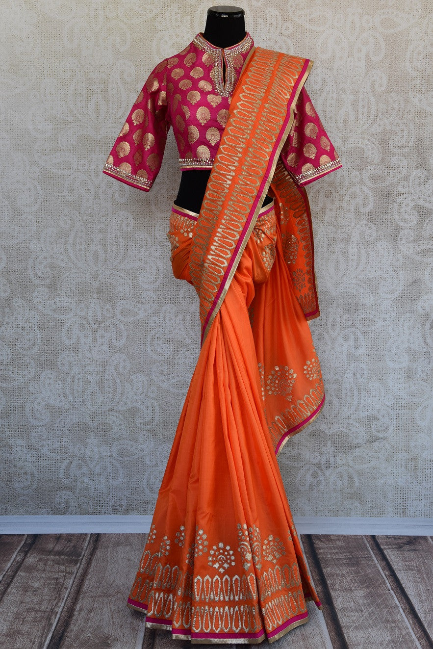 90D367 Traditional orange sari with golden applique work and pink designer blouse available at our ethnic wear store in USA - Pure Elegance. The evergreen silk saree is a great choice for Indian weddings and festive occasions.