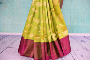90D378 Traditional silk Banarasi saree available at our ethnic Indian clothing store in USA. The floral green saree with a contrasting maroon border is a great pick for Indian weddings & receptions.