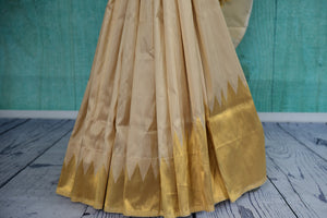 90D385 Off white and golden Banarasi silk saree available at our store Pure Elegance. This party wear saree from India will be a lovely addition to your Indian ethnic wear wardrobe.