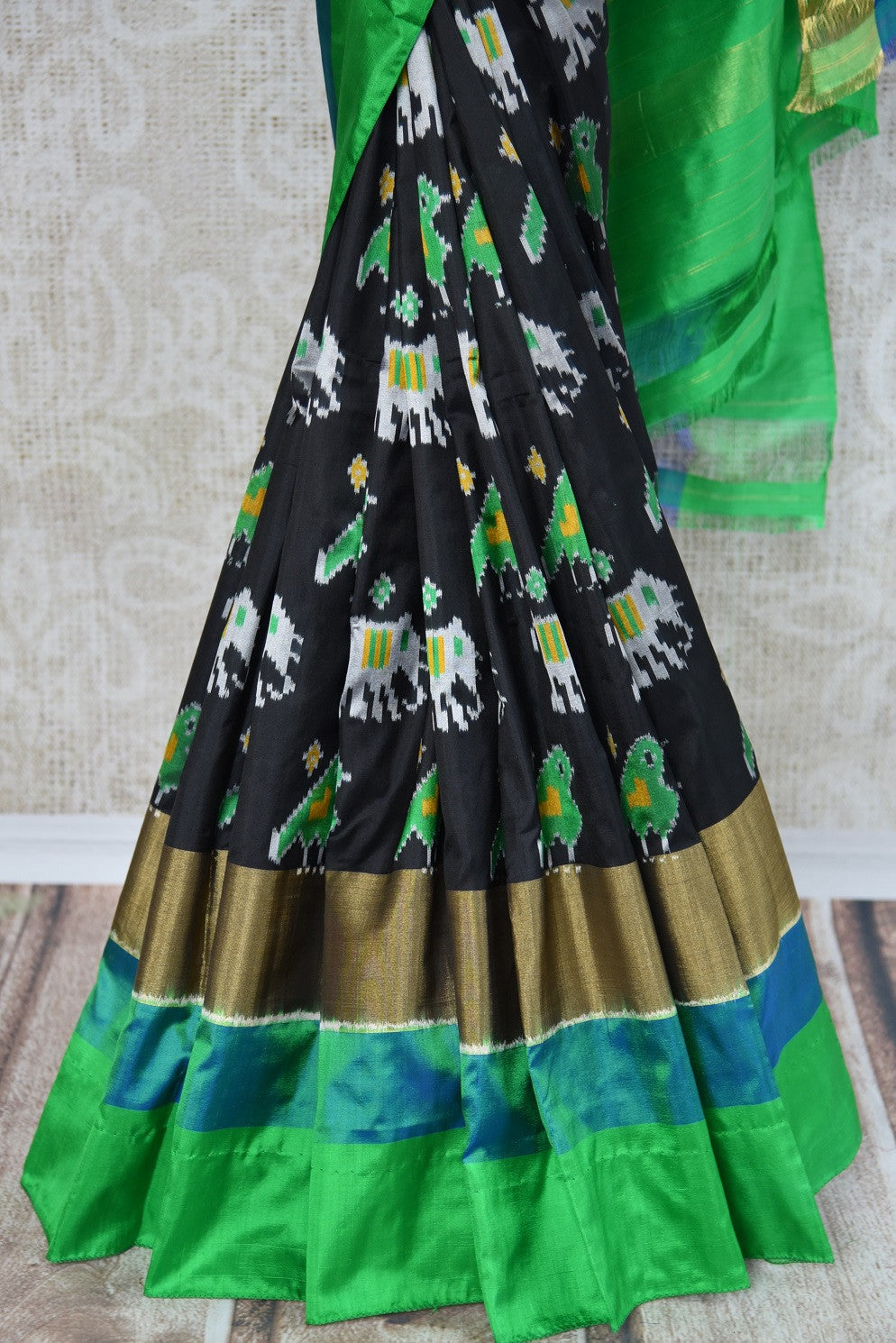 Buy this ethnic Indian black and green ikkat silk saree from Pure Elegance online or from our store in USA. Perfect for any wedding, reception or sangeet party.  Close up.