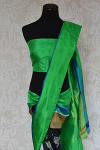 Buy this ethnic Indian black and green ikkat silk saree from Pure Elegance online or from our store in USA. Perfect for any wedding, reception or sangeet party. Front View.