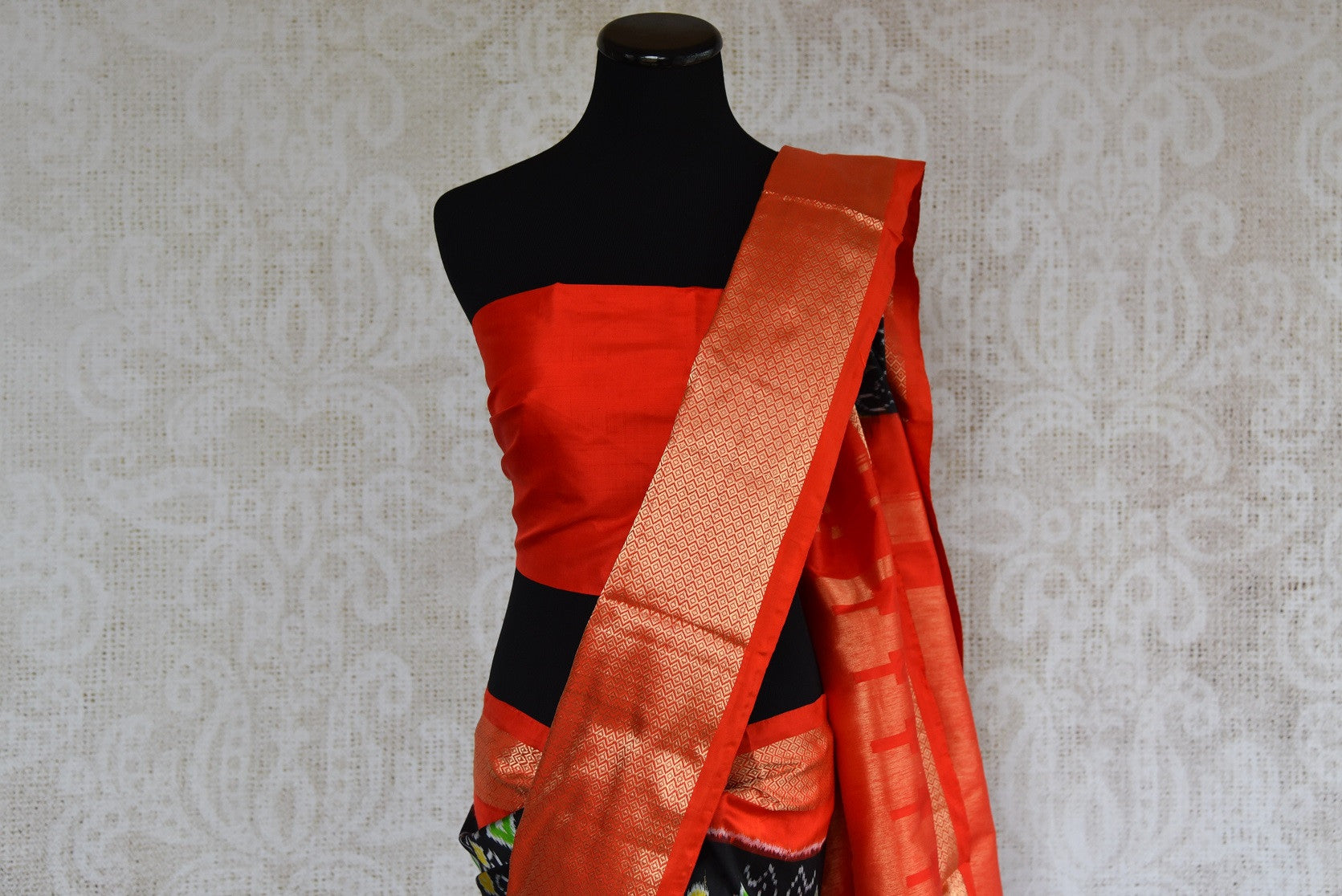 Shop this ethnic Indian orange and black ikkat silk saree online or from our Pure Elegance store in USA. Perfect for any wedding, reception, sangeet party or puja. Close up.