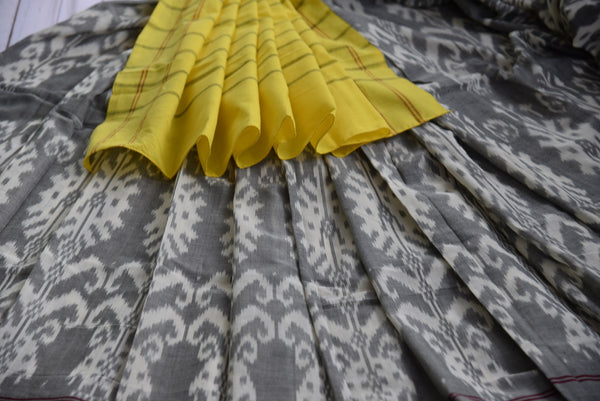 90D432 Refreshing cotton ikkat saree in grey & yellow with white design. The beautiful party wear saree can be bought at our Indian fashion store online and in Edison, USA.