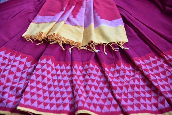90D433 Traditional red saree with pink pattern, with yellow blouse & border trims. The cotton ikkat saree is a classic ethnic outfit, available online at Pure Elegance, ideal for pujas and festivals.