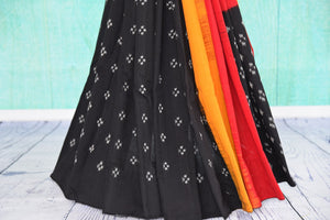 90D434 Eye-catching saree with traditional Indian design. The black cotton ikkat saree has pops of red and yellow and can be bought at our Indian clothing store in USA - Pure Elegance.