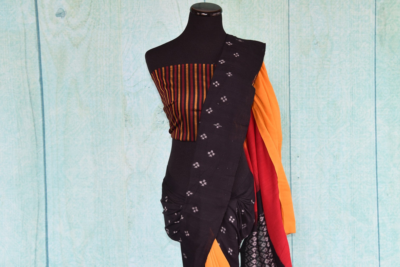 90D434 Eye-catching saree with traditional Indian design. The black cotton ikkat saree has pops of red and yellow and can be bought at our Indian clothing store online in USA - Pure Elegance.