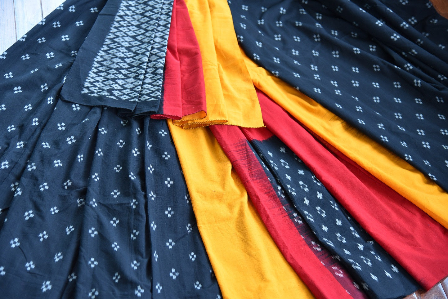 90D434 Eye-catching saree with traditional Indian design. The black cotton ikkat saree has pops of red and yellow and can be bought at Pure Elegance - our online Indian clothing store in USA.