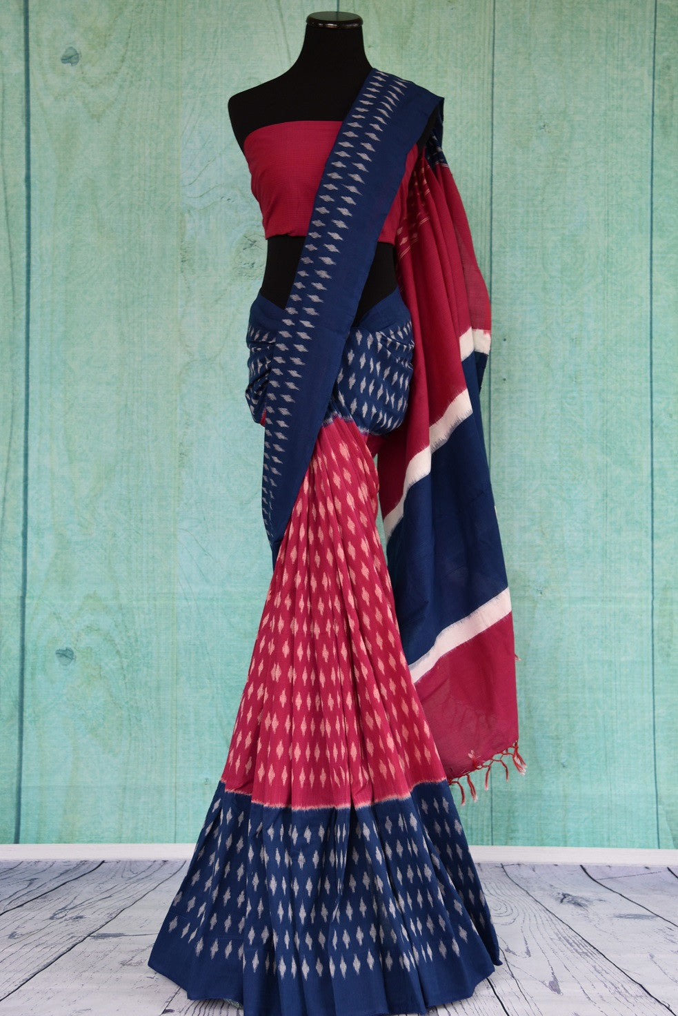 90D436 Cotton ikkat saree topped with traditional pattern & plain pallu. The evergreen red and blue sari will be a great addition to your ethnic clothing collection and is available at Pure Elegance.