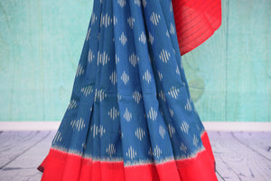 90D437 Cotton ikkat traditional saree available at our Indian clothing store in USA - Pure Elegance. The red and blue sari is perfect for occasions like pujas and Indian festivals.