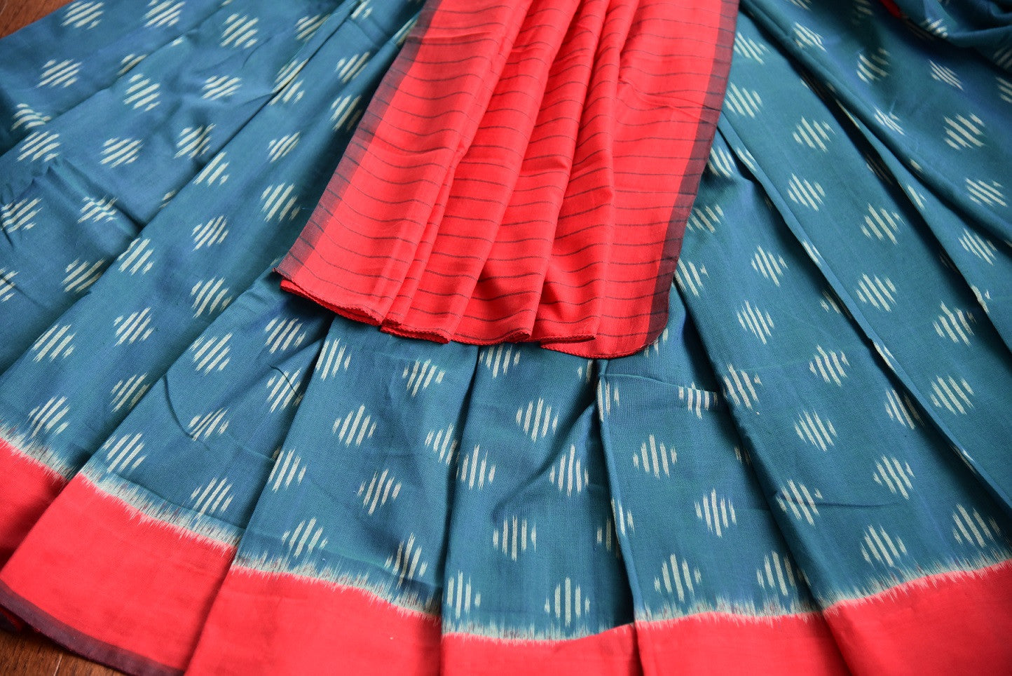 90D437 Cotton ikkat traditional saree available at our ethnic clothing store - Pure Elegance. The red and blue sari makes for a great pick for pujas and Indian festivals.