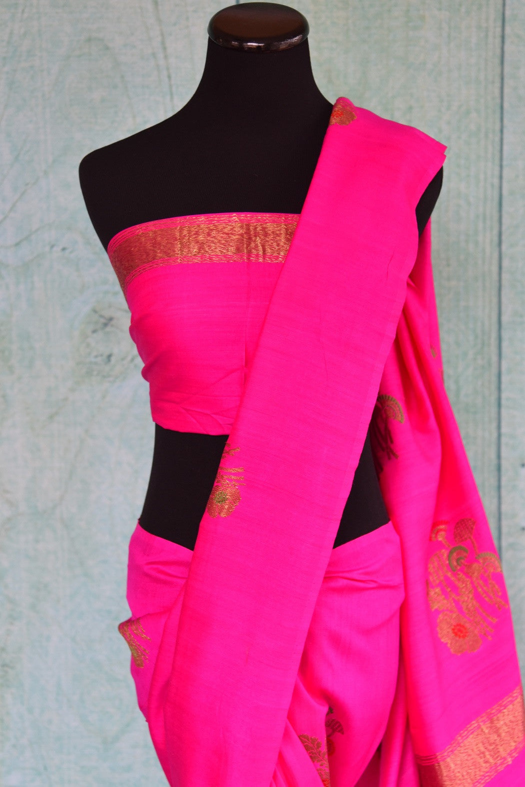 90D440 Rani pink sari with classic golden motifs, available at Pure Elegance, our Indian wear store in USA. The traditional tussar georgette Banarasi saree is ideal for Indian weddings functions.
