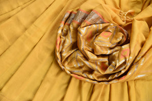 90D444 Plain yellow saree with an orange and golden patterned pallu. The tussar georgette Banarasi saree is ideal for Indian weddings and functions. Buy it online at our Indian clothing store.