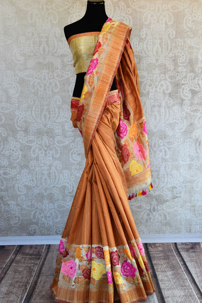 Tussar banarasi saree in orange yellow color with floral arrangement through the border and on pallu available in store Pure Elegance. Ideal pick for Parties.-Full view