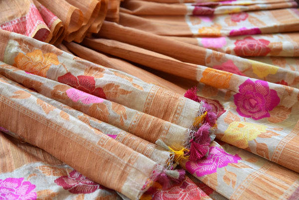 Tussar banarasi saree in orange yellow color with floral arrangement through the border and on pallu available in store Pure Elegance. Ideal pick for Parties.-close up of floral arrangement