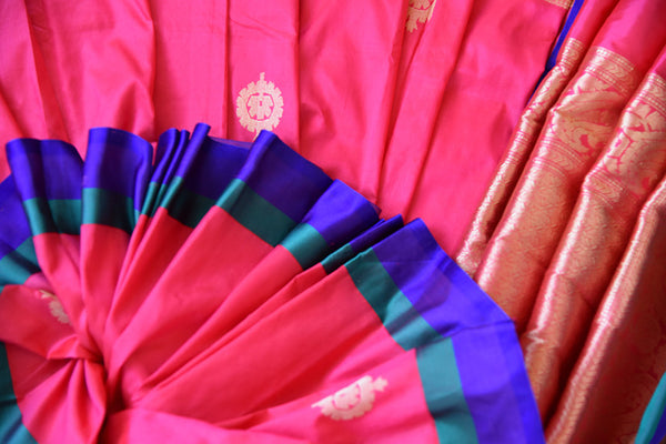 Banarasi silk in pretty pink which has gold buta and combination of blue, purple and gold available at Indian women wear store Pure Elegance, Ideal Party wear.-close up buta