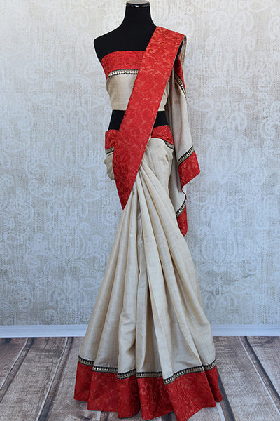 Beige tussar with thread embroidery on red silk border. Modern and chic saree on ethnic tussar perfect for Indian party.-Full view