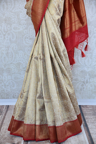 Beige and red tussar silk party saree with banarasi zari weave comes with beautiful red border and pallu.- pleats