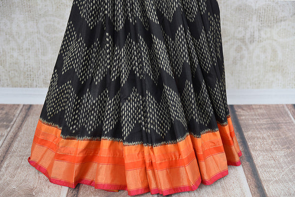 Classic black and red silk ikkat saree available at Indian women clothing store Pure Elegance in USA. Perfect ethnic saree for family gatherings and festivals.- pleats