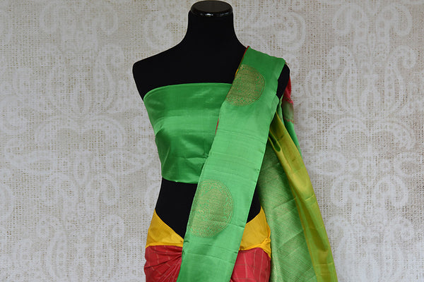 It's a red kanchivaram sari with checks in bottom with green blouse and border. It also has yellow border. Perfect traditional sari for party, festive occasion - close up view