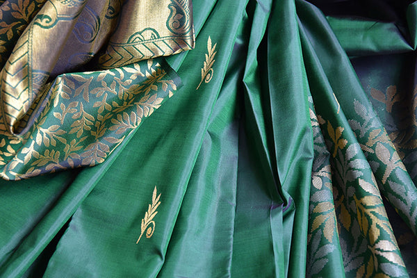 It's a woven Kanchipuram silk sari with floral design and buta in pallu. It has a plain green blouse. Perfect traditional sari for party and festive occasion. close up