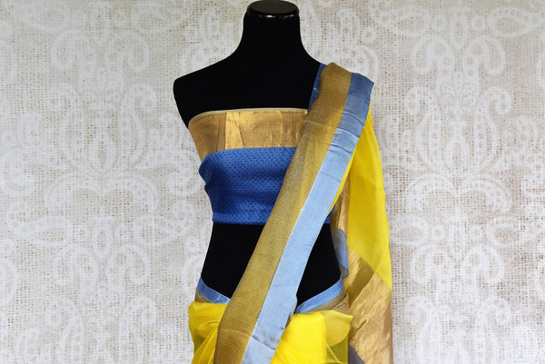 Buy this yellow zari kota sari with blue and brown borders and pallu. Comes with an elegant blue and brown blouse piece. Buy from Pure Elegance online USA store. - top
