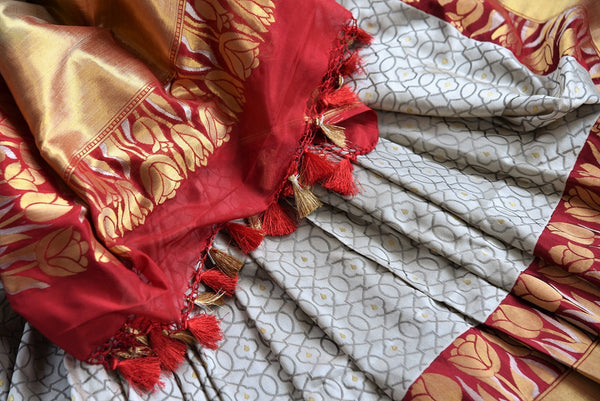 This beautiful Indian off white banarasi silk saree is decorated with stunning designs and a flashy red and gold border. Comes with a red and gold blouse piece. Buy from Pure Elegance online USA Store. - close up