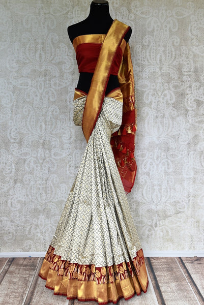 This beautiful Indian off white banarasi silk saree is decorated with stunning designs and a flashy red and gold border. Comes with a red and gold blouse piece. Buy from Pure Elegance online USA Store. - full