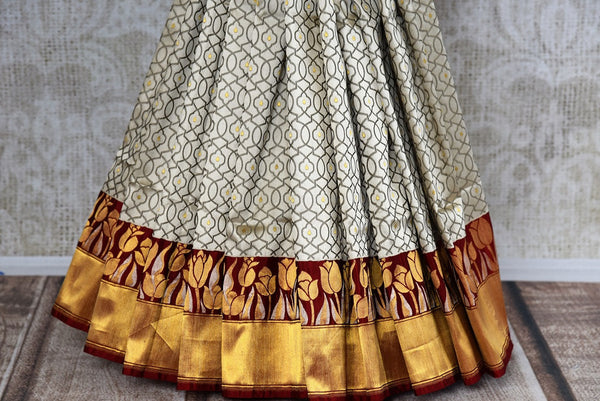 This beautiful Indian off white banarasi silk saree is decorated with stunning designs and a flashy red and gold border. Comes with a red and gold blouse piece. Buy from Pure Elegance online USA Store. - bottom