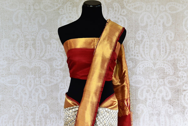 This beautiful Indian off white banarasi silk saree is decorated with stunning designs and a flashy red and gold border. Comes with a red and gold blouse piece. Buy from Pure Elegance online USA Store. - top