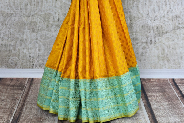 Buy Mustard Yellow Banarasi Silk Saree online with Zari border and buta from Pure Elegance store. Exclusive collection of pure woven Banarasi Sarees for Indian women.-pleats