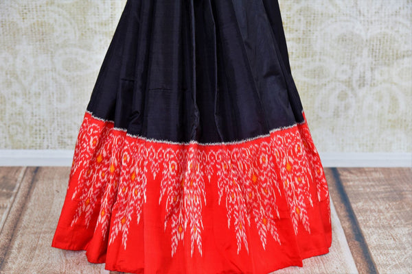 Buy classic black silk saree online in USA with red ikkat border from Pure Elegance. Our Indian fashion store brings an alluring range of silk ikkat sarees in USA.-pleats