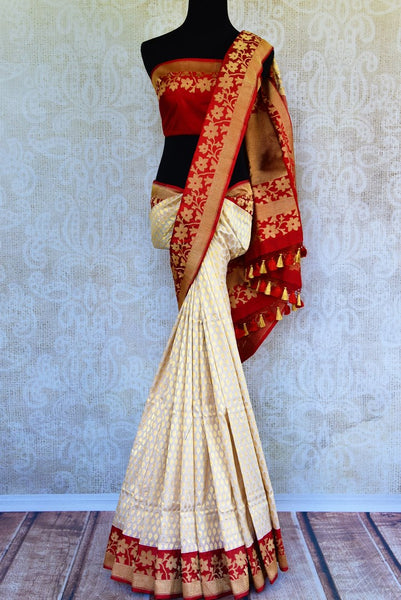 Buy off white Banarasi silk saree online in USA with red floral border. Get your hands on ethnic Indian woven Banarasi silk sarees at Pure Elegance online store in USA now.-full view