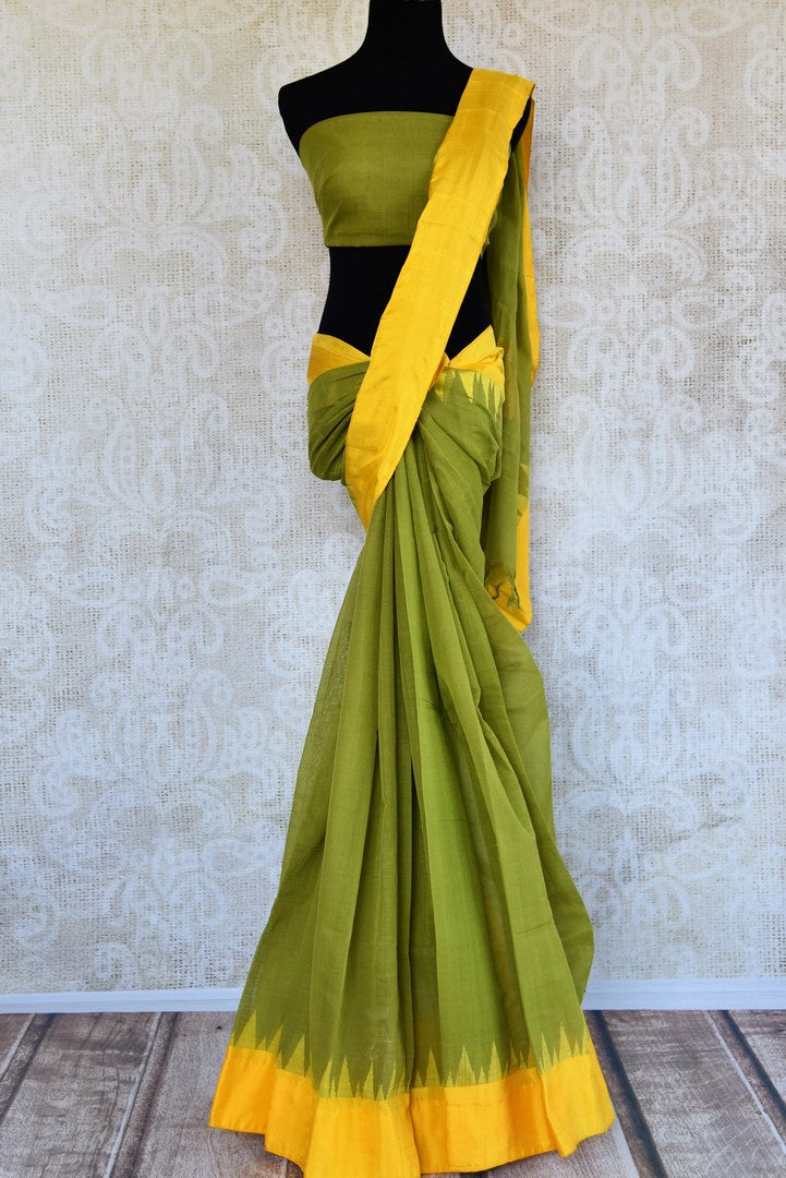 Buy green ikat khaddi sari online in USA with yellow border. Pure Elegance clothing store brings an alluring collection of ethnic Indian ikat saris in USA for women. -full view