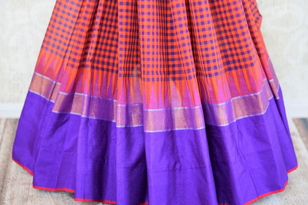 Buy orange checked ikat khaddi sari online in USA with blue border. Pure Elegance clothing store brings an alluring collection of Indian ikkat saris in USA for women. -pleats