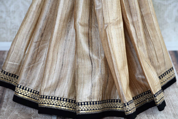 Buy beige half kalamkari print and half plain silk sari online in USA with embroidery. Pure Elegance clothing store brings exquisite range of Indian sarees in USA for women.-pleats