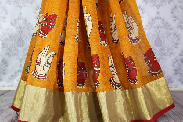 Buy bright orange chanderi silk sari online in usa with dancing hands print. The saree is adorned with a bright gold border making it a perfect occasionwear. For more such elegant Indian designer saris in USA, shop at Pure Elegance Indian clothing store or visit online.-pleats