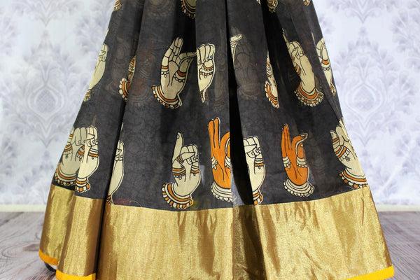 Buy greyish black chanderi silk saree online in usa with dancing hands print. The saree is adorned with a bright gold border making it perfect for an ethnic look. For more such elegant Indian designer saris in USA, shop at Pure Elegance Indian clothing store or visit online.-pleats