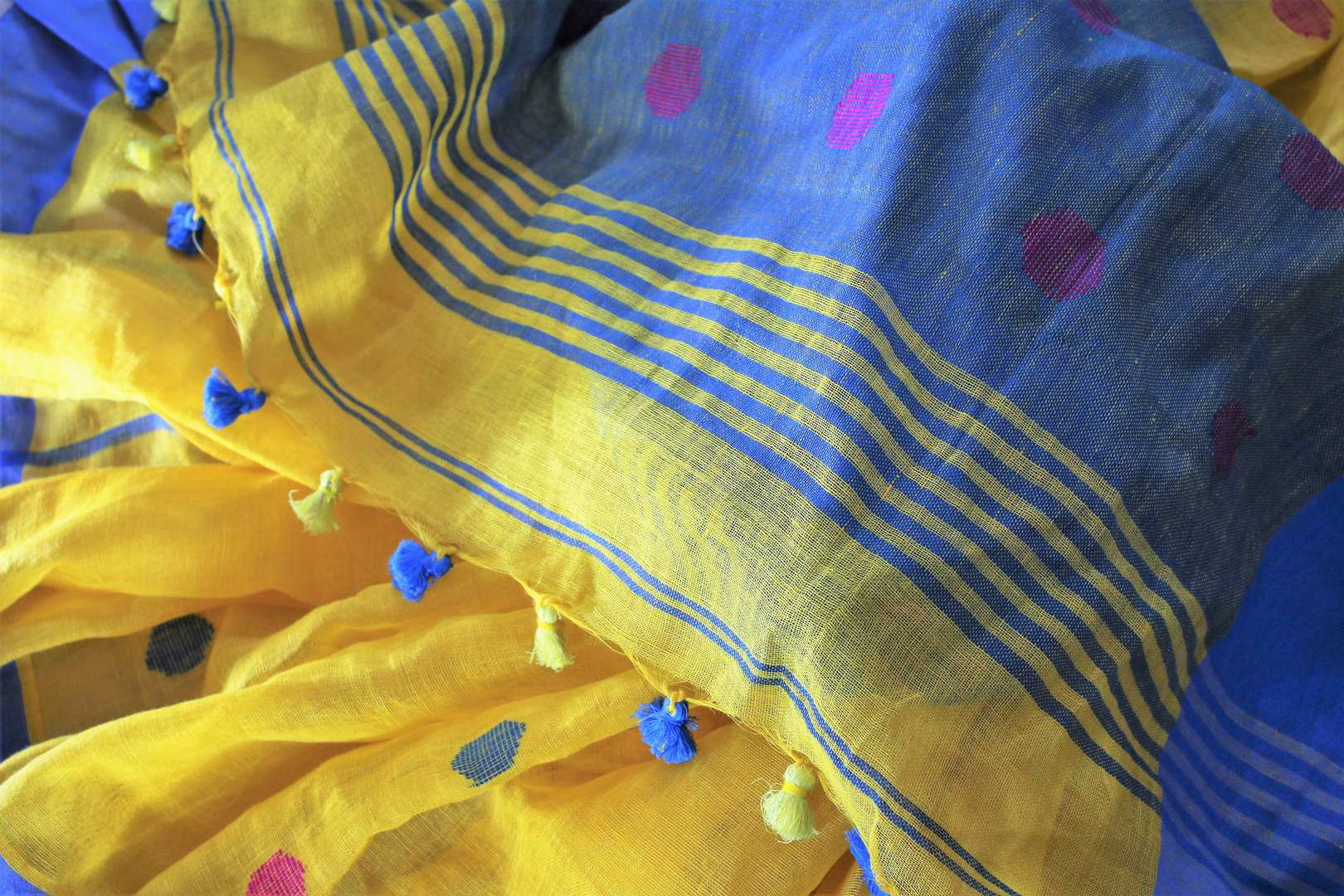 Buy online ethnic yellow linen saree in USA. The saree is contrasted with yellow border and pallu and bright pink butas which makes it so striking. Shop beautiful Indian handloom saris in USA at Pure Elegance fashion store for a beautiful Indian saree look.-details