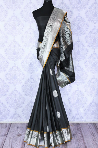 Buy elegant black Kanjivaram silk sari online in USA. The saree is richly decorated with beautiful silver zari border and peacock buta . For more such beautiful Indian Kanchipuram silk saris in USA shop at Pure Elegance fashion store for a stunning traditional look.-full view