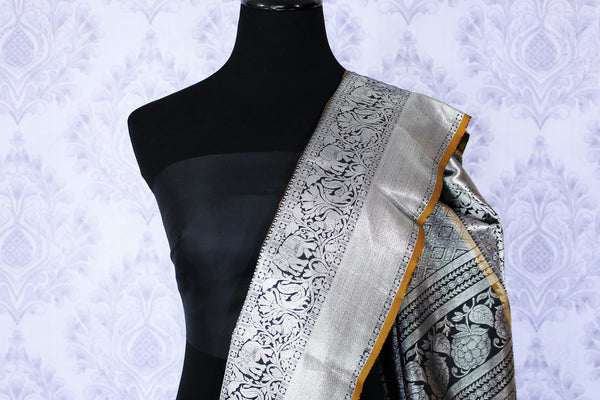 Buy elegant black Kanjivaram silk sari online in USA. The saree is richly decorated with beautiful silver zari border and peacock buta . For more such beautiful Indian Kanchipuram silk saris in USA shop at Pure Elegance fashion store for a stunning traditional look.-blouse pallu