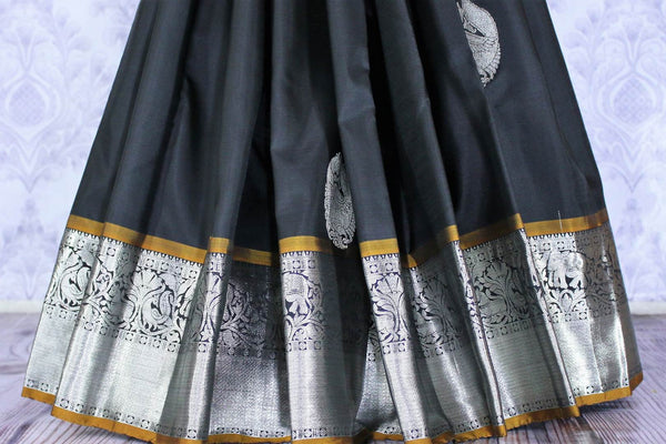 Buy elegant black Kanjivaram silk sari online in USA. The saree is richly decorated with beautiful silver zari border and peacock buta . For more such beautiful Indian Kanchipuram silk saris in USA shop at Pure Elegance fashion store for a stunning traditional look.-pleats