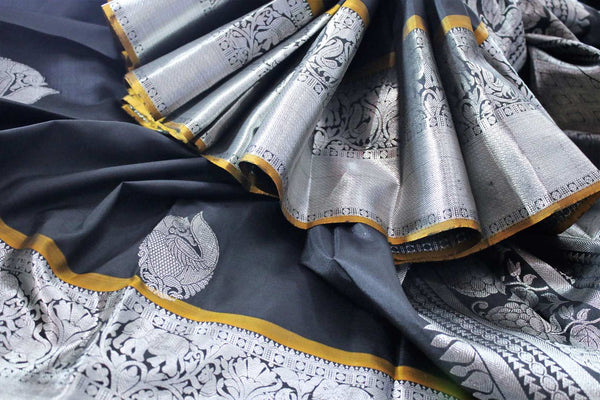 Buy elegant black Kanjivaram silk sari online in USA. The saree is richly decorated with beautiful silver zari border and peacock buta . For more such beautiful Indian Kanchipuram silk saris in USA shop at Pure Elegance fashion store for a stunning traditional look.-details