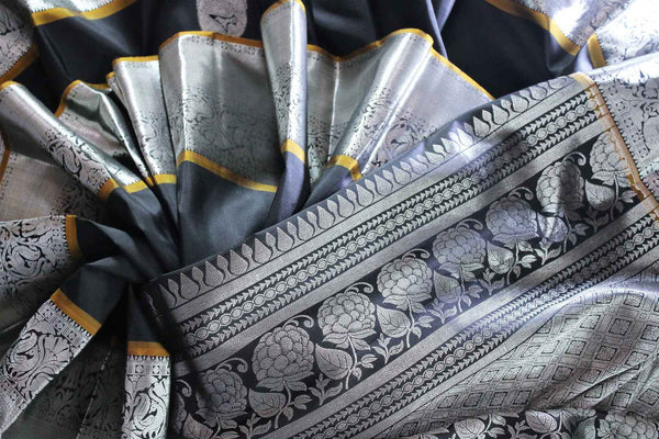 Buy elegant black Kanjivaram silk sari online in USA. The saree is richly decorated with beautiful silver zari border and peacock buta . For more such beautiful Indian Kanchipuram silk saris in USA shop at Pure Elegance fashion store for a stunning traditional look.-closeup